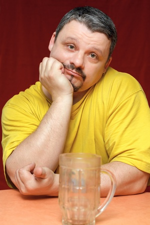 lustful: close-up portrait dark sad man looks at an empty beer mug