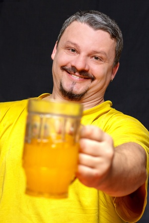 lustful: close-up portrait dark happy man holding a glass of beer, shallow depth of field
