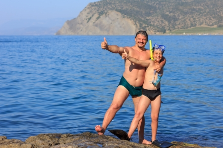 happy laughing father and son with a scuba mask on the sea beach photo