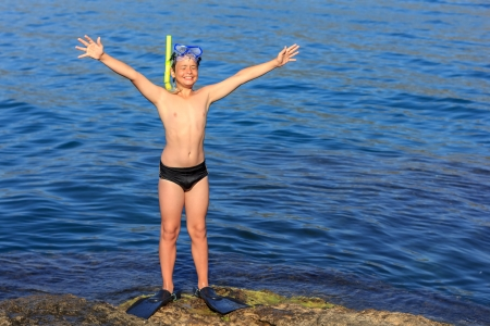 happy laughing boy of twelve in the scuba mask and fins on the sea beach photo