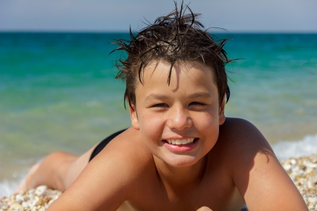 happy laughing boy of twelve lying on the sea beach photo