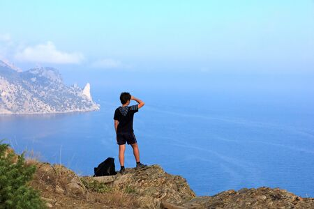 Young traveler looks at the beautiful Crimean seascape from the top of the mountain, the mountain Karaul-Oba, Sudak, Crimea, Ukraine photo