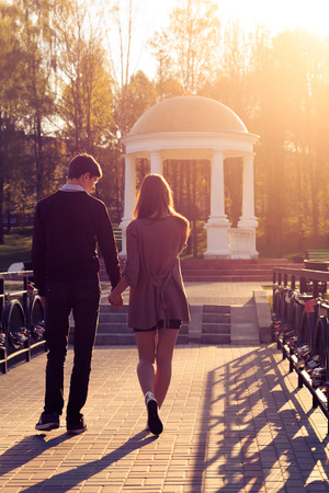 Young fashion elegant stylish couple posing in a European city park at dawn  Hipster cute girl with handsome man having fun outdoor  photo