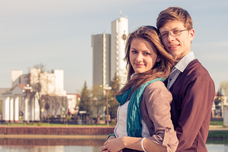 Young fashion elegant stylish couple posing in a European city park  Hipster cute girl with handsome man having fun outdoor  photo