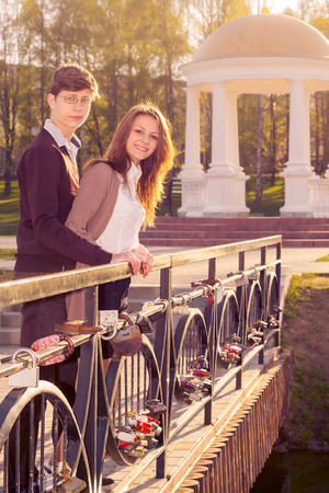 Young fashion elegant stylish coupl ein love posing on the bridge lovers. Hipster cute girl with handsome man having fun outdoor. photo