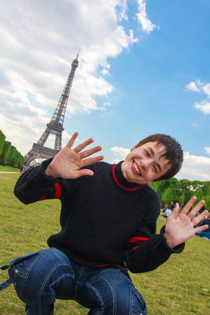 la tour eiffel: Teenager laughing, playing and fooling around on the Champ de Mars in front of the Eiffel Tower  La Tour Eiffel  in Paris