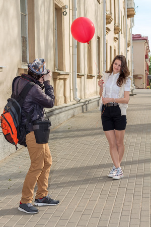 beautiful fashion girl top model with red baloon posing for a photograph hipster morning on an empty city street photo