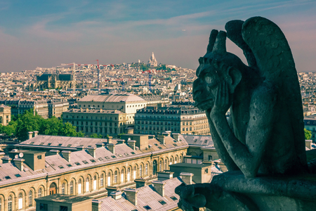 The Stryge  most famous of the Chimeres  looking toward Basilica of the Sacred Heart of Jesus at Notre Dame Cathedral in Paris photo