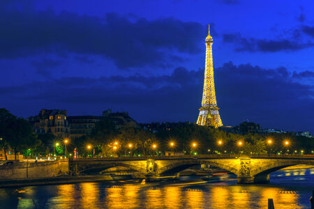 PARIS - MAY 9  Cityscape of Paris with Eiffel Tower  Tour Eiffel  and Pont des Invalides at night illumination on May 9, 2014  The Eiffel tower is the most famous and visited monument of France