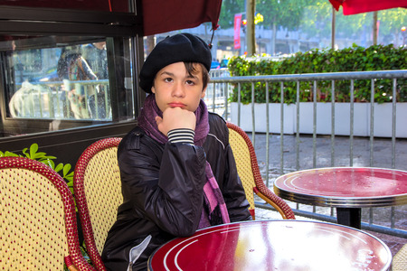 elysees: 13 year old teenager in a French beret and scarf sitting at a table Parisian cafe on the Champs Elysees