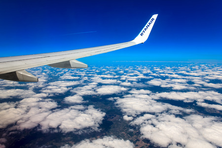 scheduled: VILNIUS, LITHUANIA - MAY 2  Looking through window aircraft Ryanair during flight in wing on 2 may 2014  Ryanair is one of the largest low-cost European airline by scheduled passengers carried