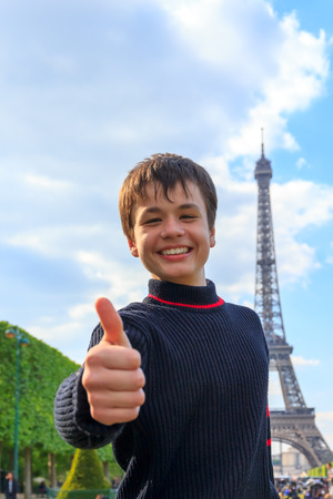 la tour eiffel: Cheerful teenager shows thumb up sitting on the Esplanade des Invalides in Paris , France Stock Photo