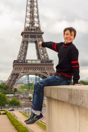 la tour eiffel: Cheerful teenager shows the Eiffel tower  La Tour Eiffel  in Paris, France Stock Photo