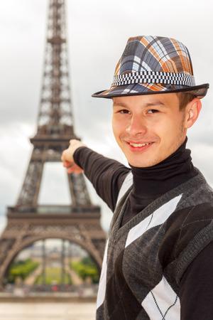 la tour eiffel: Young man hipster in a hat and vest shows the Eiffel tower  La Tour Eiffel  in Paris, France Stock Photo