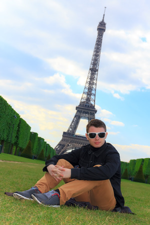 Young man hipster sits on the Champ de Mars near the Eiffel tower  La Tour Eiffel  in Paris, France photo