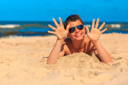Happy laughing boy of thirteen on the sea beach shows the hands in the sand. Shallow depth of field, focus on hands and face photo