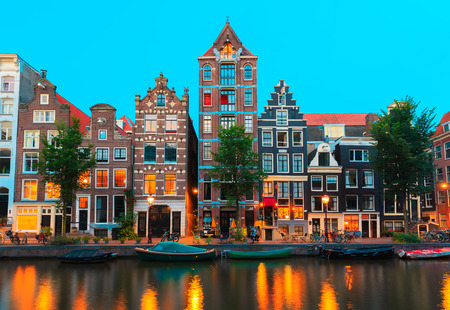 Night city view of Amsterdam canals and typical houses, boats and bicycles, Holland, Netherlands.  Stockfoto