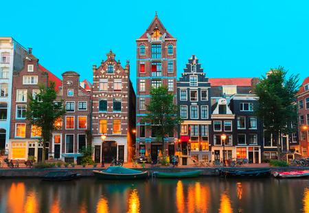 Noční pohled na město z amsterdamských vodních kanálů a typických domů, lodí a jízdních kol, Holandsko, Nizozemsko.