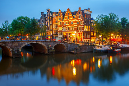 Night city view of Amsterdam canal, bridge and typical houses, boats and bicycles, Holland, Netherlands.