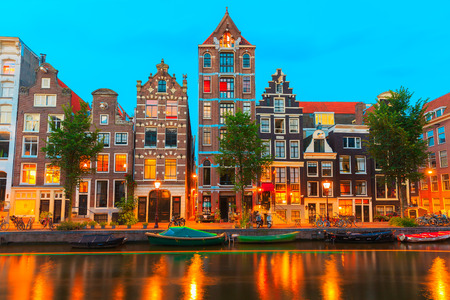 Night city view of Amsterdam canal Herengracht with typical dutch houses, boats and bicycles, Holland, Netherlands