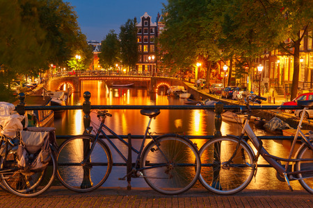 Night  illumination of Amsterdam canal and bridge with typical dutch houses, boats and bicycles, Holland, Netherlands   photo