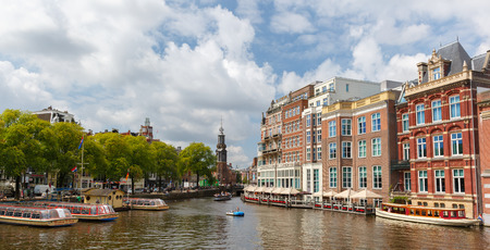 Amsterdam, Netherlands - July 30,2014  Cityscape with the river Amstel and Munttoren tower in Amsterdam  Canal ring area placed on the UNESCO World Heritage List