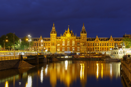 railway history: Night city view of Amsterdam canal and Centraal Station, Holland, Netherlands  Long exposure