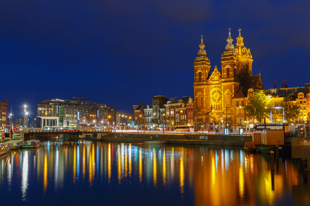 Night city view of Amsterdam canal and Basilica of Saint Nicholas, Holland, Netherlands Long exposure