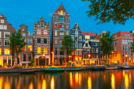 Night city view of Amsterdam canal Herengracht, typical dutch houses and boats, Holland, Netherlands