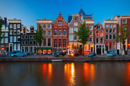 Night city view of Amsterdam canal, typical dutch houses and boats, Holland, Netherlands photo