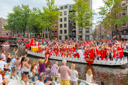 canal parade: Amsterdam, Netherlands - August 2, 2014: Participants at the famous Canal Parade of the Amsterdam Gay Pride 2014 on the Prinsengracht canal in Amsterdam. The parade is one of the biggest public events in the Netherlands, every year it is visited by more t Editorial
