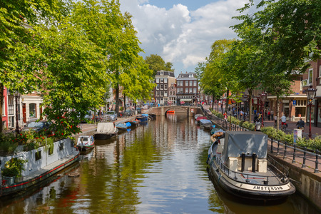 Amsterdam, Netherlands - August 05,2014: City view of Amsterdam canals and typical houses, boats and bicycles. Canal ring area placed on the UNESCO World Heritage List.