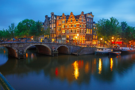 Night city view of Amsterdam canal, bridge and typical houses, boats and bicycles, Holland, Netherlands. photo