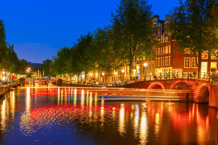 dutch landmark: Night city view of Amsterdam canal with bridges and luminous track from the boat, Holland, Netherlands.