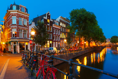 canal street: Night city view of Amsterdam canal, bridge with typical houses and bicycles, Holland, Netherlands.
