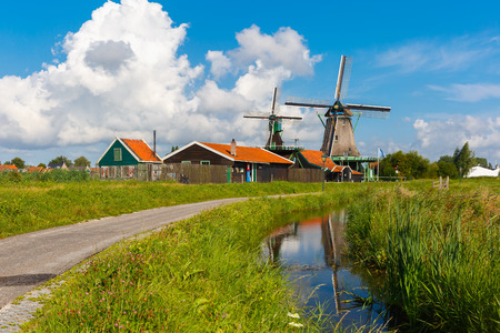 Picturesque rural landscape with windmills in Zaanse Schans close to canal, Holland, Netherlands photo