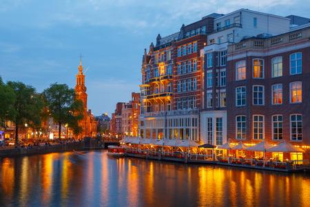 canal street: Night city view of Amsterdam canal, bridge and Munttoren tower, Holland, Netherlands. Stock Photo