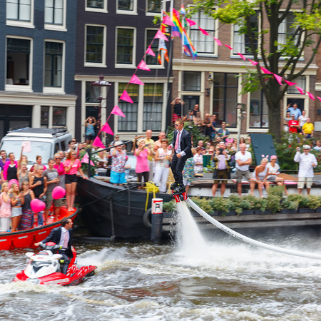 canal parade: Amsterdam, Netherlands - August 2, 2014: Participants at the famous Canal Parade of the Amsterdam Gay Pride 2014. Focus on the central person.