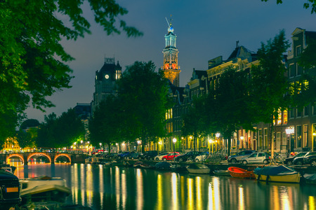 westerkerk: Night city view of Amsterdam canal and Westerkerk church, boats and bridge, Holland, Netherlands. Toning. Stock Photo