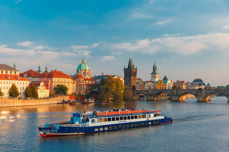 Prague, Czech Republic - October 3, 2014: Tourist boat in front Charles Bridge and Old Town in at evening. Prague - one of the most beautiful cities in Europe, a popular tourist center. Among the main attractions of Prague 18 magnificent bridges.