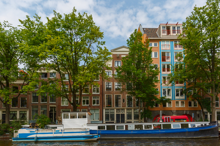 City view of Amsterdam canal, typical houses and boats, Holland, Netherlands. photo