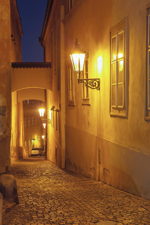 praga: Narrow cobbled street of the old town at night in Mala Strana, Prague, Czech Republic