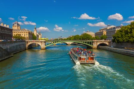 Tourist boat near Conciergerie and bridge Pont Notre-Dame over river Seine in Paris, France
