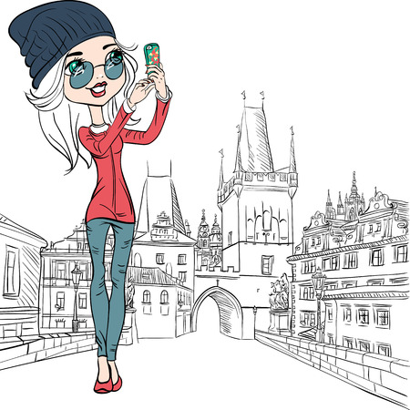 Cute beautiful fashionable girl makes selfie on the Charles Bridge in Prague