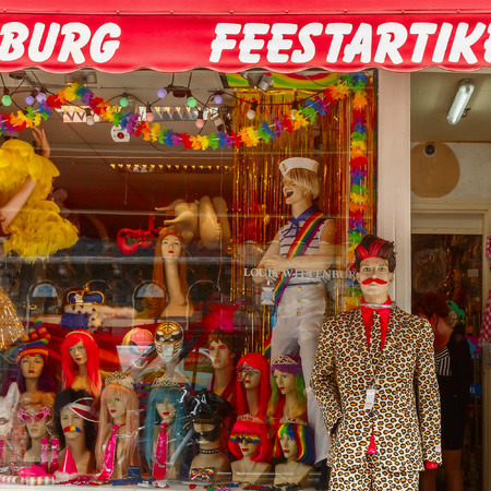 the trappings: Amsterdam, The Netherlands - July 29, 2014: storefront clothing, wigs and accessories with gay trappings during the Amsterdam Gay Pride. Every year the parade is visited by more than 400000 people.