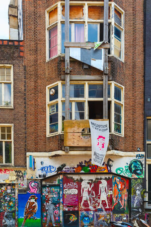 vandalize: Amsterdam, Netherlands - August 1, 2014: Urban graffiti on a dilapidated house on the street Spui