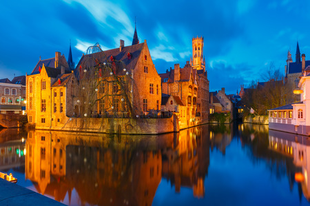 Scenic cityscape with a medieval fairytale town and tower Belfort from the quay Rosary, Rozenhoedkaai, at sunset in Bruges, Belgium photo