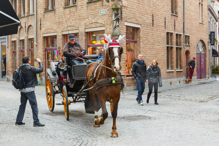 horse drawn: Bruges, Belgium - December 26, 2014: Horse carriage and tourists on the streets of Brugge Christmas. Belgian city of Bruges (Brugge) is UNESCO world heritage listed for its medieval center.