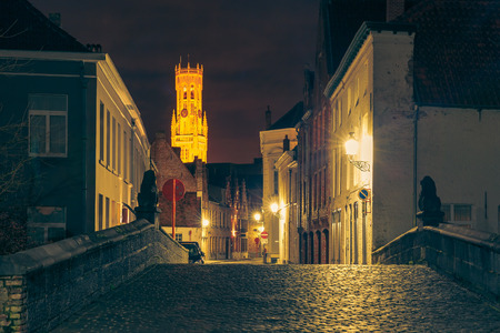 belfort: Cityscape with a picturesque night street and tower Belfort in Bruges Stock Photo