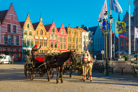 horse drawn carriage: Bruges, Belgium - December 28, 2014: Horse carriage waiting tourists on Grote Markt square of Brugge Christmas. Belgian city of Bruges is UNESCO world heritage listed for its medieval center.
